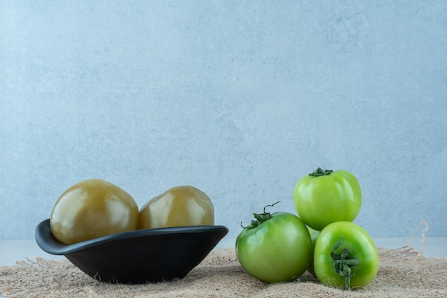 A bowl of picked tomatoes next to a pile of green tomatoes on a burlap, on the marble.