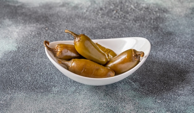 Bowl of pickled green jalapeno peppers on gray table