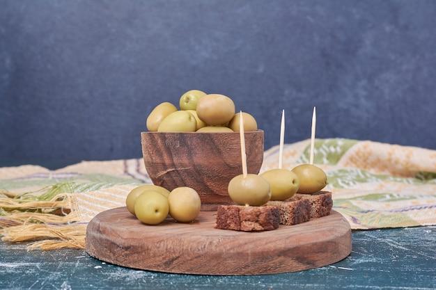 Ciotola di olive in salamoia sul blu con la tovaglia.