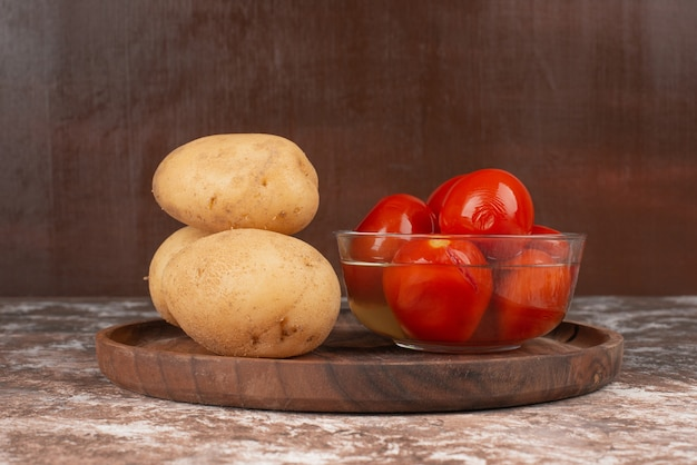 Bowl of pickled tomatoes and boiled potato on wooden plate.