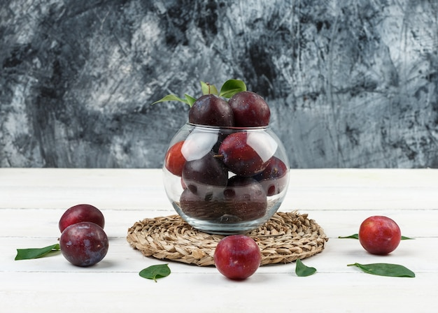 A bowl of plums on a wicker placemat on a dark blue marble and white wooden board background. close-up.