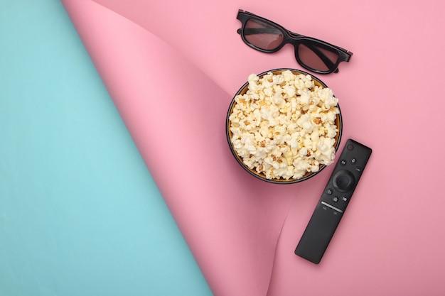 Bowl of popcorn, 3d glasses, tv remote on blue pink