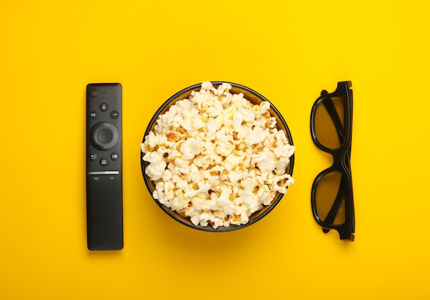 Bowl of popcorn, 3d glasses, tv remote on yellow