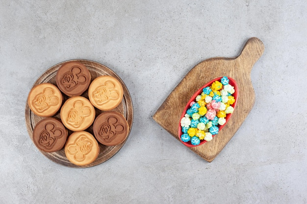 Ciotola di caramelle popcorn e biscotti decorati sul vassoio in legno su sfondo marmo. foto di alta qualità