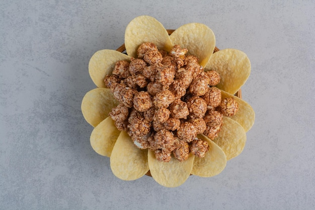 Bowl of popcorn candy and potato chips on marble surface