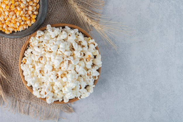 Bowl of popcorn, jug of corn and a wheat stalk on a piece of cloth on marble surface