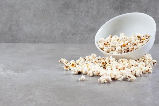 Ciotola di popcorn sparsi su sfondo marmo. foto di alta qualità