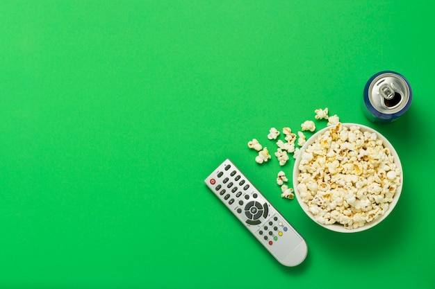 Bowl of popcorn, a tv remote, a can with a drink on a green background. concept of watching tv, film, tv series, sports, shows at your leisure.