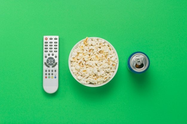 Bowl of popcorn, a tv remote, a can with a drink on a green background.