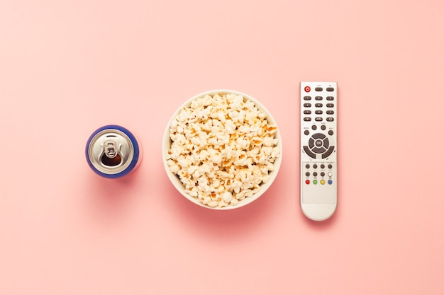 A bowl of popcorn, a tv remote, a jar of drink on a pink background. the concept of watching tv, film, tv series, sports, shows. flat lay, top view.