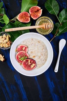 A bowl of porridge with figs slices and walnuts.