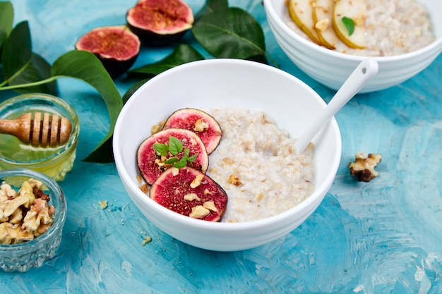 A bowl of porridge with figs slices and walnuts