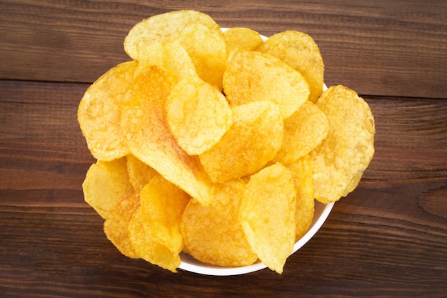 Bowl of potato chips on wooden background