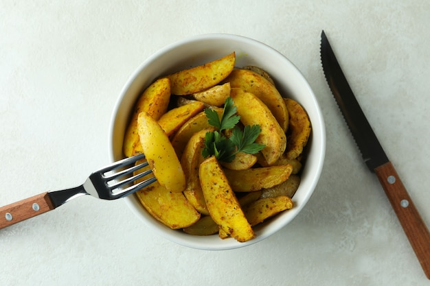 Bowl of potato wedges and cutlery on white textured