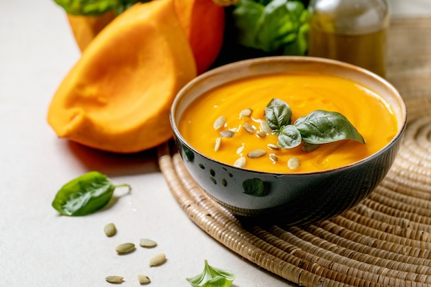 Bowl of pumpkin or carrot vegetarian cream soup decorated by fresh basil