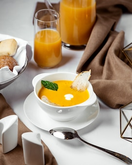 A bowl of pumpkin soup garnished with toast and cream