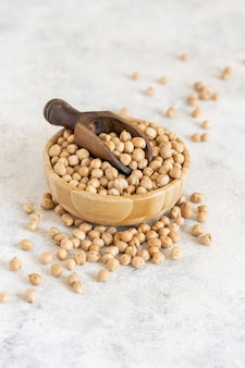 Bowl of raw dry chickpea with a scoop on a white table close up