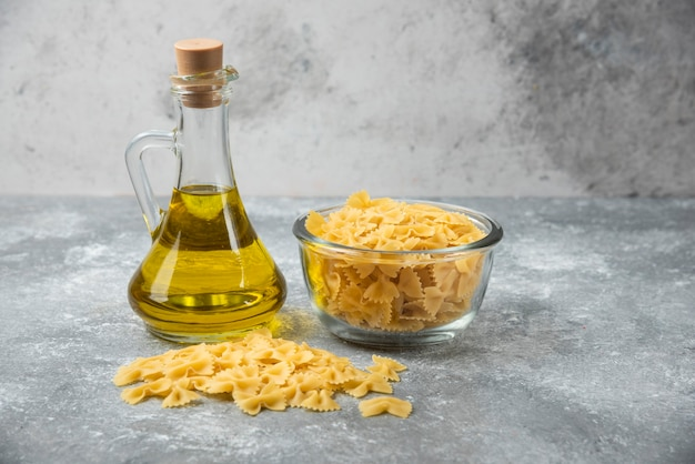 Bowl of raw farfalle pasta with bottle of olive oil on marble background.