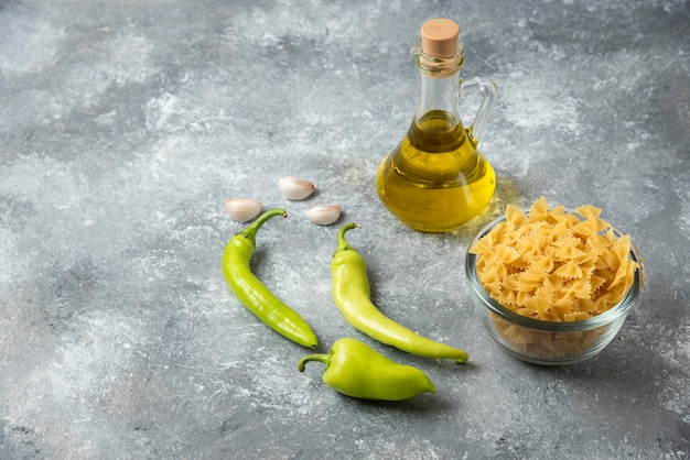 Bowl of raw farfalle pasta with bottle of olive oil and vegetables on marble background.