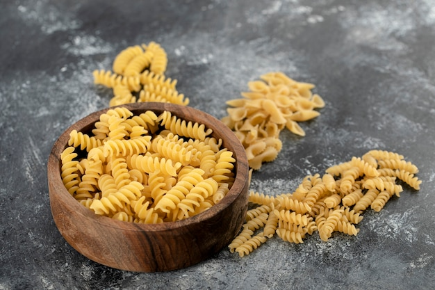 Bowl of raw fusilli pasta on marble surface