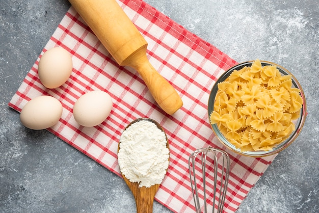 Bowl of raw pasta, eggs, spoon of flour and rolling pin on marble table with tablecloth.