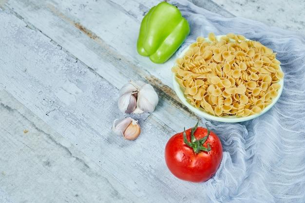 Una ciotola di pasta cruda con pomodoro, pepe e aglio.