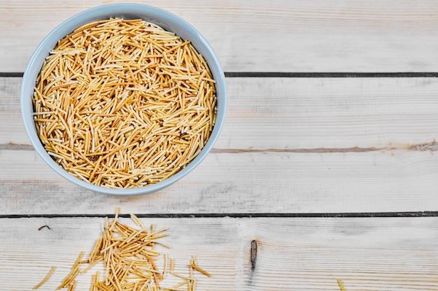 Una ciotola di pasta cruda sul tavolo di legno