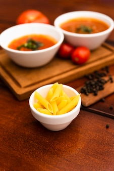 Bowl of raw penne pasta with tomato sauce and black peppercorn on wooden table