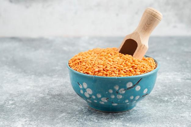 Ciotola di lenticchie rosse crude sulla tavola di marmo con il cucchiaio.