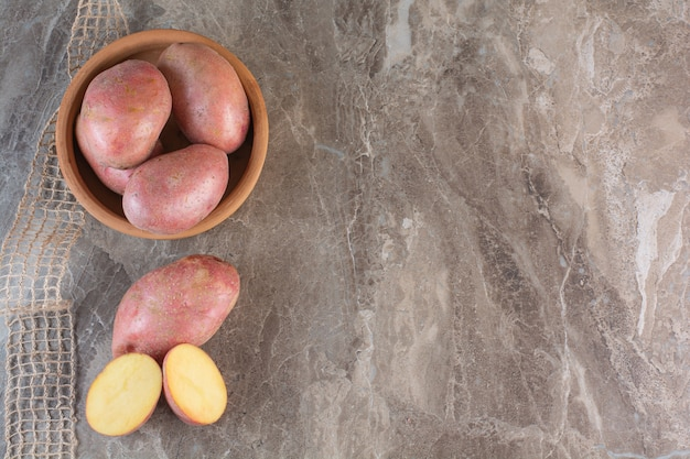 Bowl of raw sweet potatoes placed marble background.