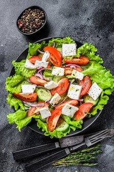 Bowl of ready-to-eat greek salad. black table. top view.