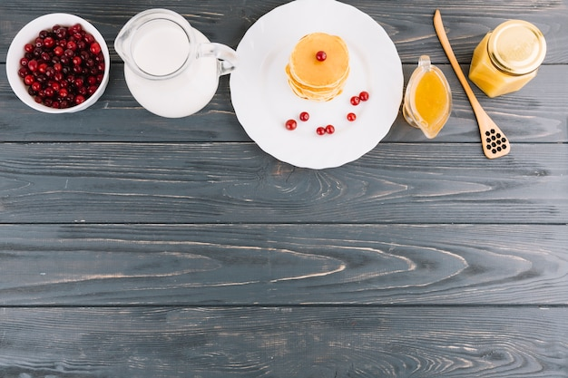Bowl of red currants berries; milk; honey and pancakes on wooden textured backdrop
