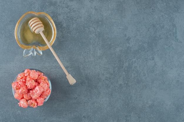 Ciotola di caramelle popcorn rosse e un piccolo piattino di miele con un cucchiaio di miele su sfondo marmo. foto di alta qualità