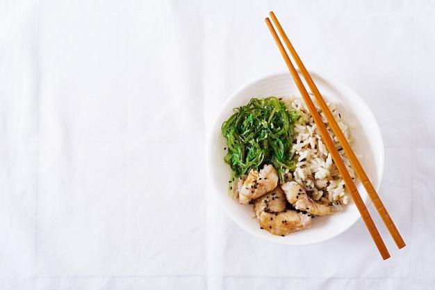 Bowl of rice, boiled white fish and wakame chuka or seaweed salad.  top view. flat lay