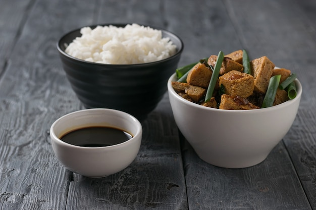 A bowl of rice and a bowl of tofu cheese on a wooden table. vegetarian asian dish.