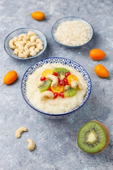 Bowl of rice flakes porridge with kiwi slices, pomegranate seeds, cumquats and cashew nuts, top view
