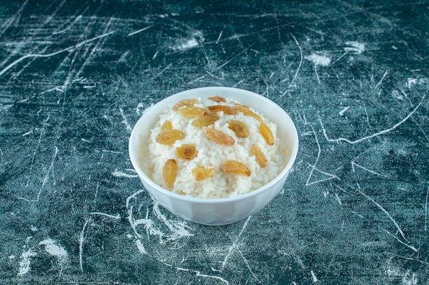 A bowl of rice pudding with raisins , on the blue background. high quality photo