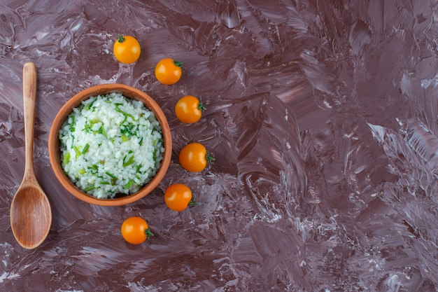 Bowl of rice , small tomatoes and spoon on the marble surface
