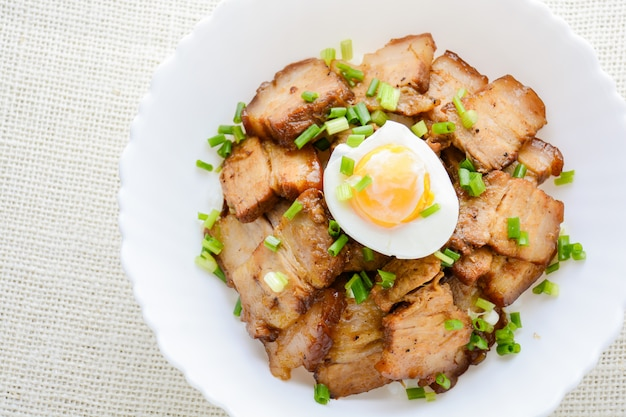 Bowl of rice topped with braised pork belly and boiled egg