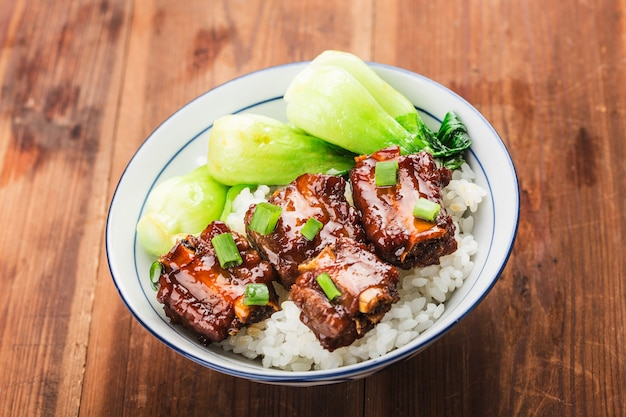 A bowl of rice with ribs in brown sauce