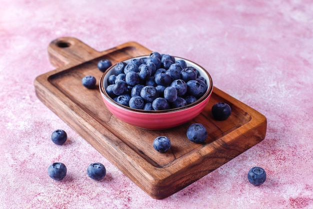Bowl of ripe fresh blueberries on wooden cutting board