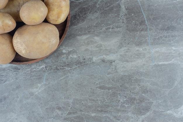 Una ciotola di patate mature sul tavolo di marmo.