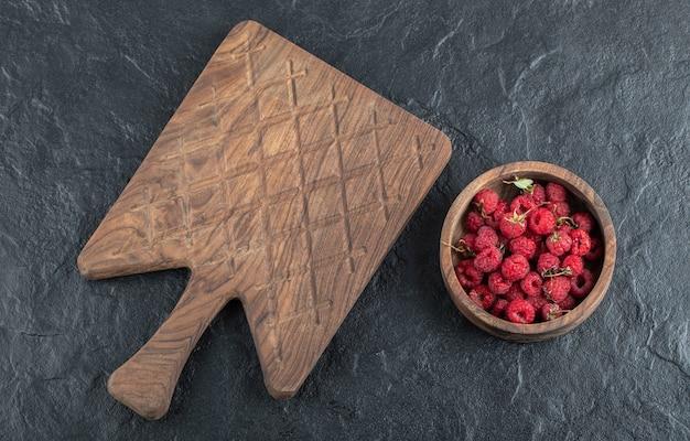 Ciotola di lamponi maturi con tavola di legno.