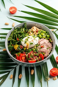 Bowl of roast beef pokeh with poached egg and vegetables