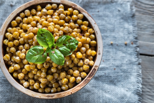 Bowl of roasted chickpeas on the wooden surface