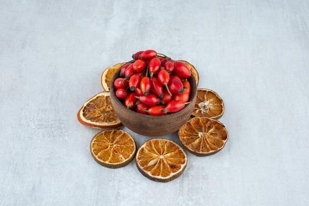 Ciotola di cinorrodi e fette d'arancia essiccate sulla superficie della pietra.