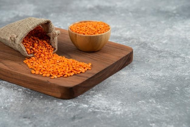 Ciotola e sacco di lenticchie rosse crude su tavola di legno.