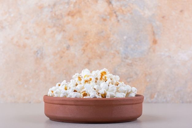 Bowl of salted popcorn for movie night on white background. high quality photo