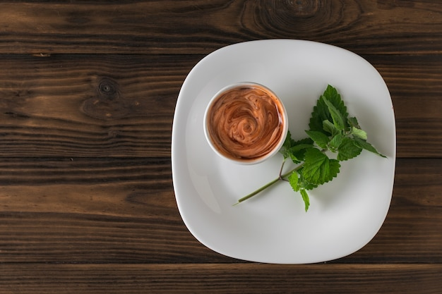 A bowl of sauce and a sprig of green herbs on a wooden table. vegetarian sauce. sauce for meat and fish. flat lay.