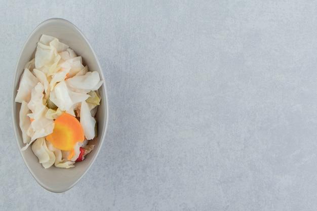 Una ciotola di crauti con carote, sulla superficie di marmo